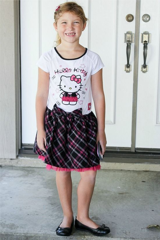 girl wearing a Hello Kitty dress in black, pink, and white.