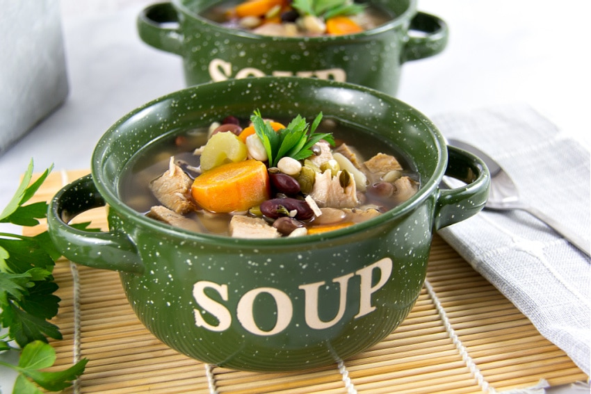 a 15 bean soup with turkey and carrots in a green soup bowl