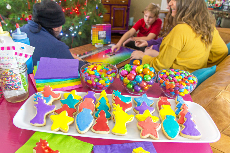 Brightly colored Christmas cookies on a tray with matching candy and the Hues and Cues board game