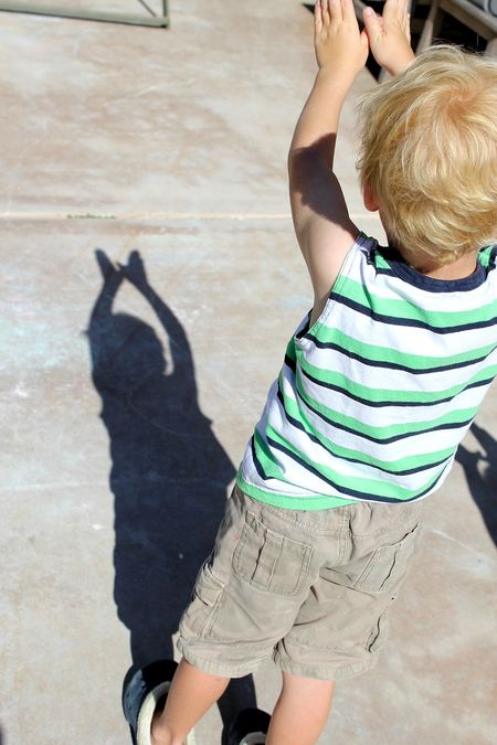 a boy making a butterfly shadow in the sun