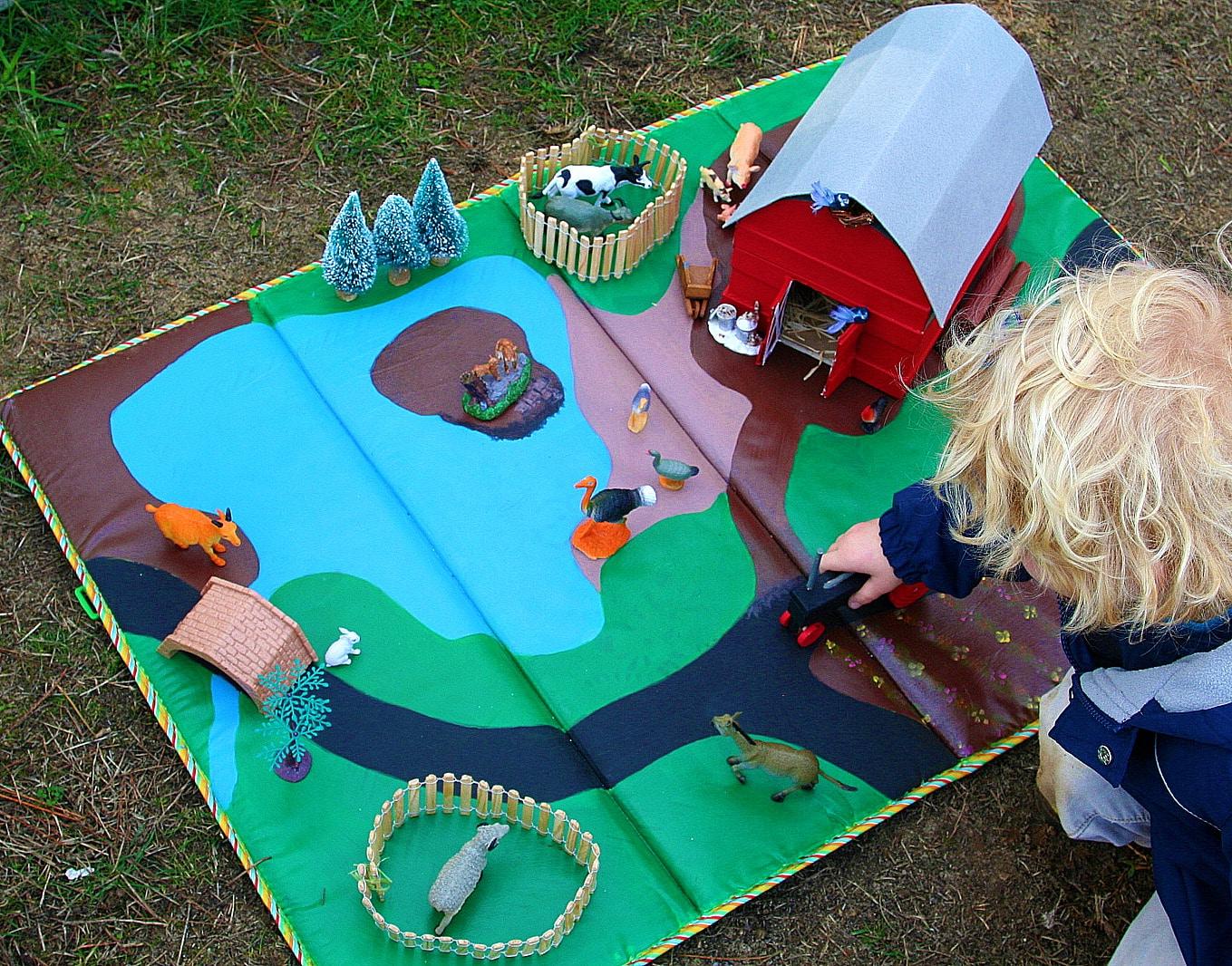 A boy playing with a handmade barn on a farm play mat.