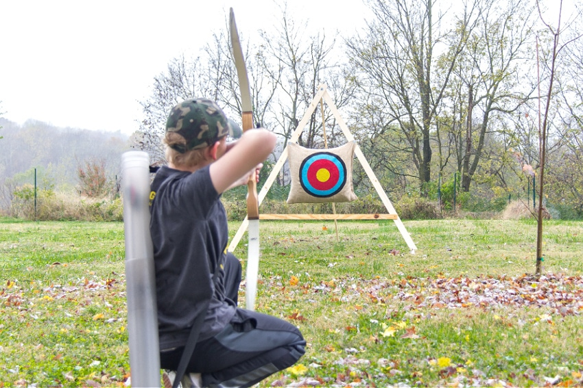 A boy aiming an archery bow and arrow at a homemade target.