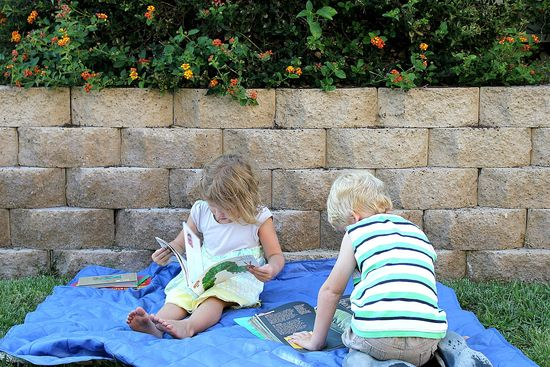 kids reading books about butterflies and caterpillars on a picnic blanket