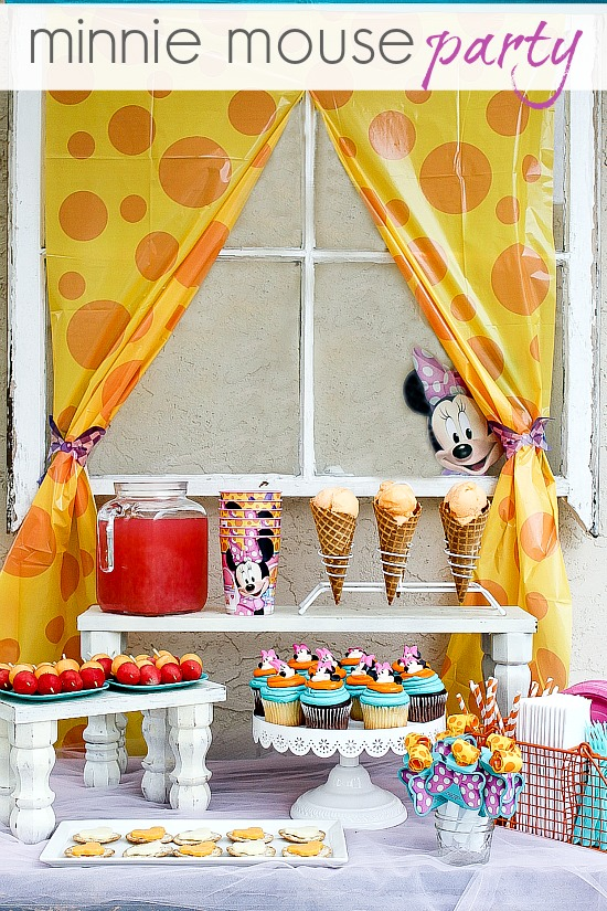 a Minnie Mouse party table with fun food and decorations