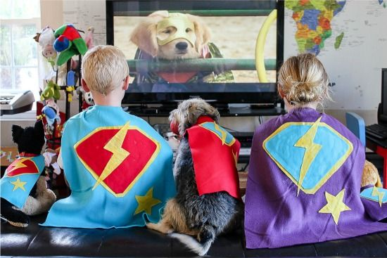 Kids and dogs wearing handmade super hero capes while watching Disney Super Buddies