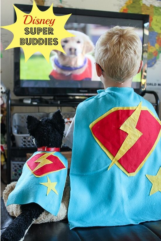 A boy and toy dog wearing super hero capes while watching Disney Super Buddies