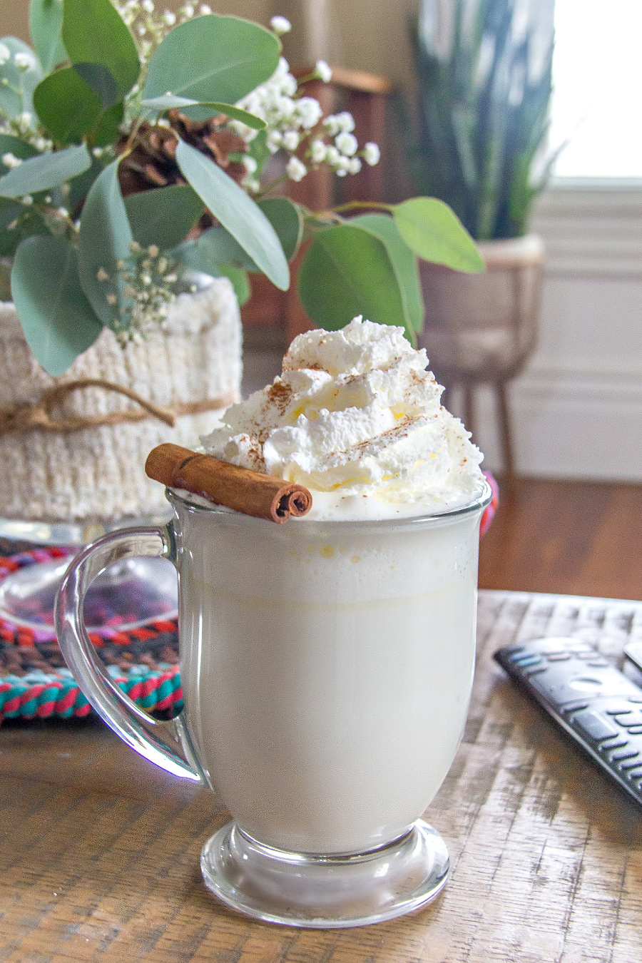 white hot chocolate topped with a cinnamon stick and ground cinnamon in a clear mug