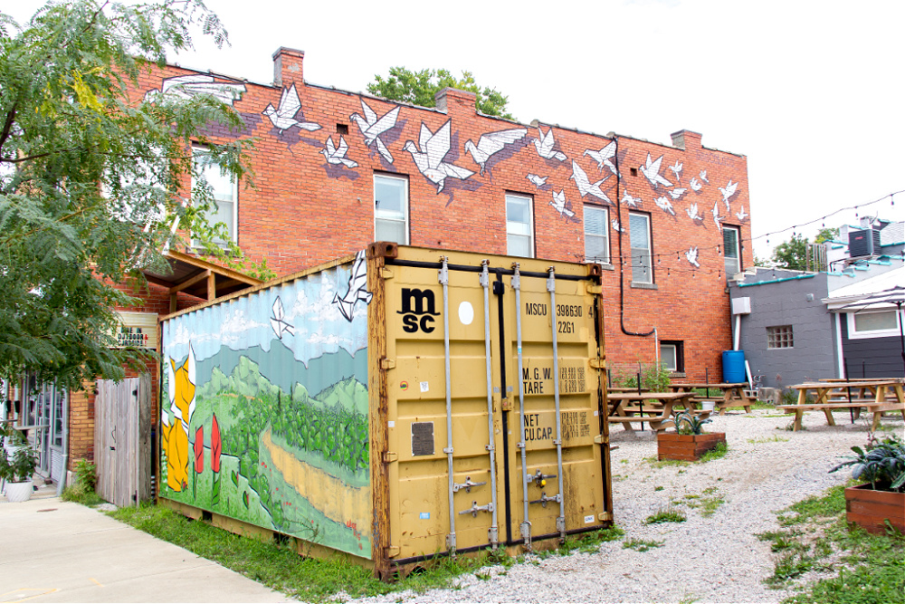 The Origami Tsunami mural by BroCoLoco and the fox container mural by The Art of Joe King at Broomwagon Bikes and Cafe in Lexington