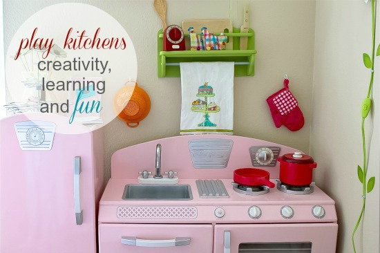 A pink kitchen for kids with kitchen accessories for role playing.