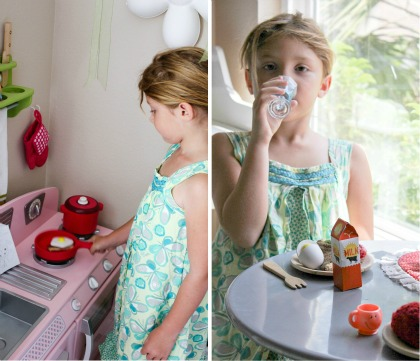 A little girl cooking eggs on her play kitchen and having breakfast together.