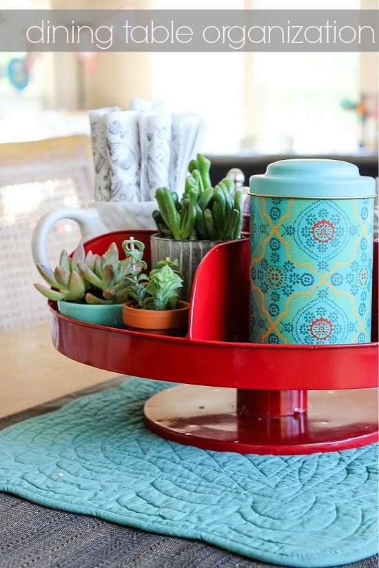 A red hardware bin on top of a dining table with organized compartments for napkins and condiments.
