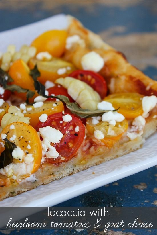 focaccia bread on a white tray topped with heirloom tomatoes, goat cheese, and corn