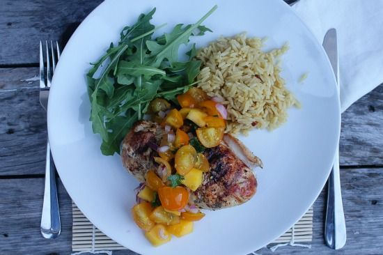 yellow tomato salsa over grilled chicken and served with rice and greens.
