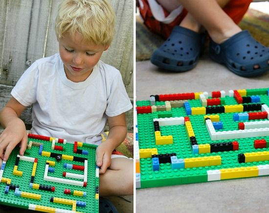 a boy playing with a LEGO marble maze