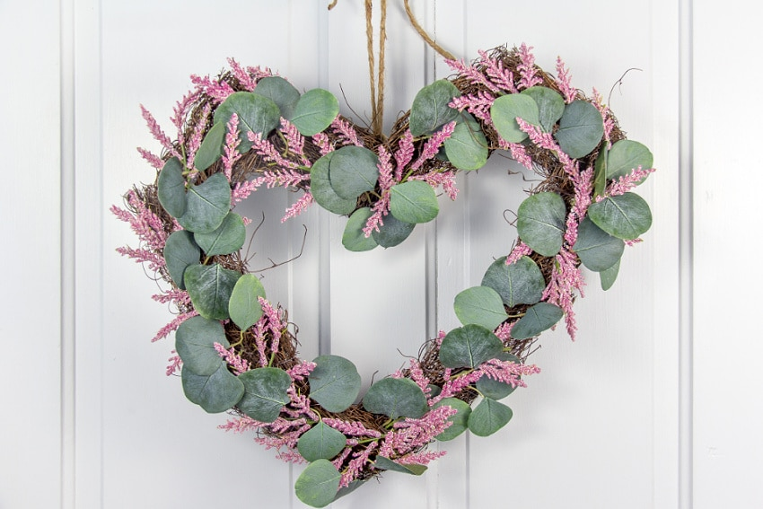 a stick heart-shaped wreath with pink flowers and leaves hanging on a white door