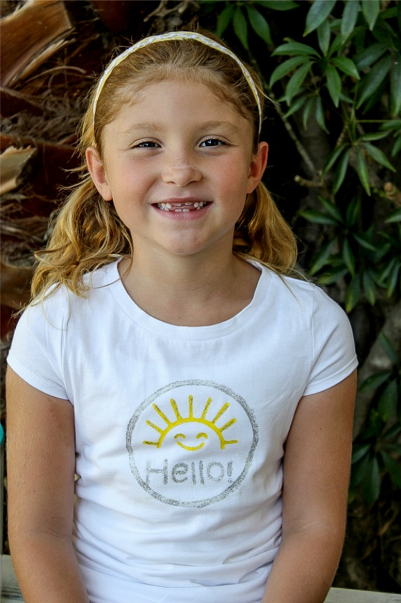 A girl wearing a white t-shirt stamped with hello sunshine.