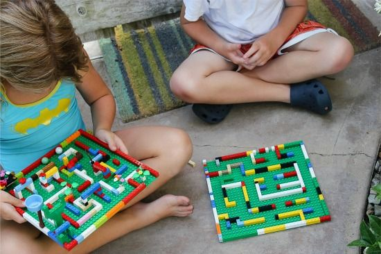 a girl and boy playing with LEGO marble mazes