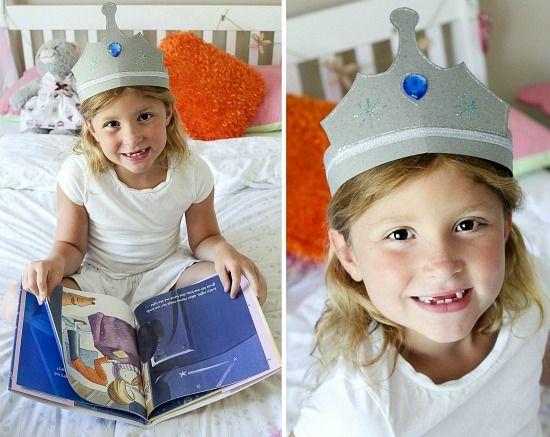 A little girl wearing a paper crown and reading Zoe's Room No Sisters Alloweed