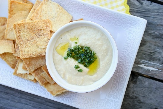 hummus topped with olive oil and parsley and served with pita chips