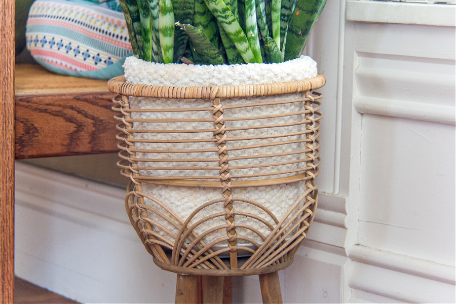 A knitted cozy for a potted plant inside a can plant stand.