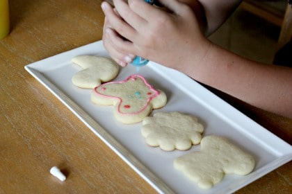 a girl decorating spring cookies with icing