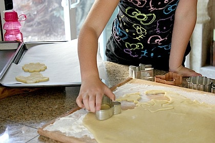 a girl cutting out cookies from rolled out cookie dough