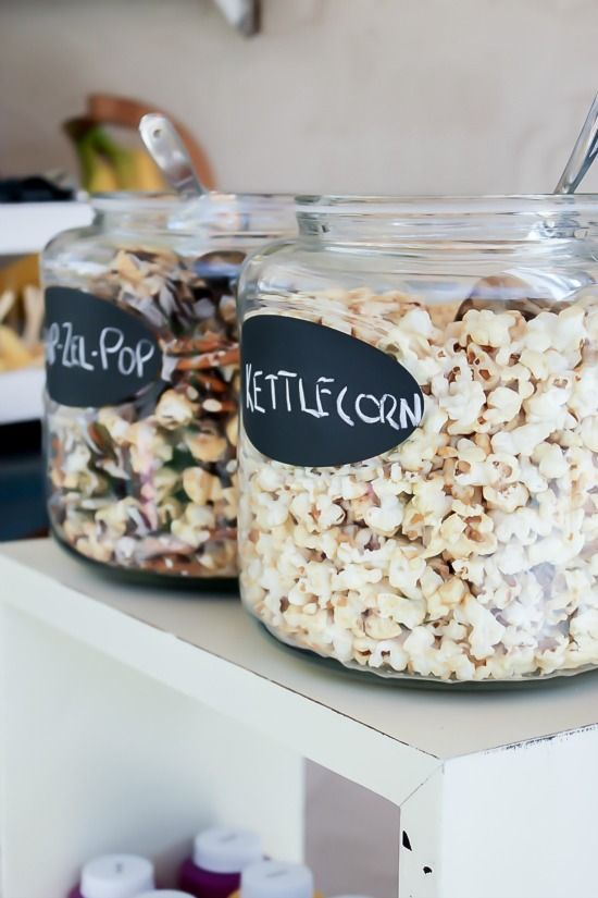 Popcorn in large glass jars with scoops for a movie night.
