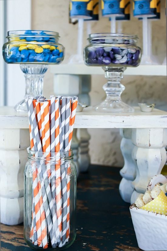 Paper straws in glass jars for a party table.