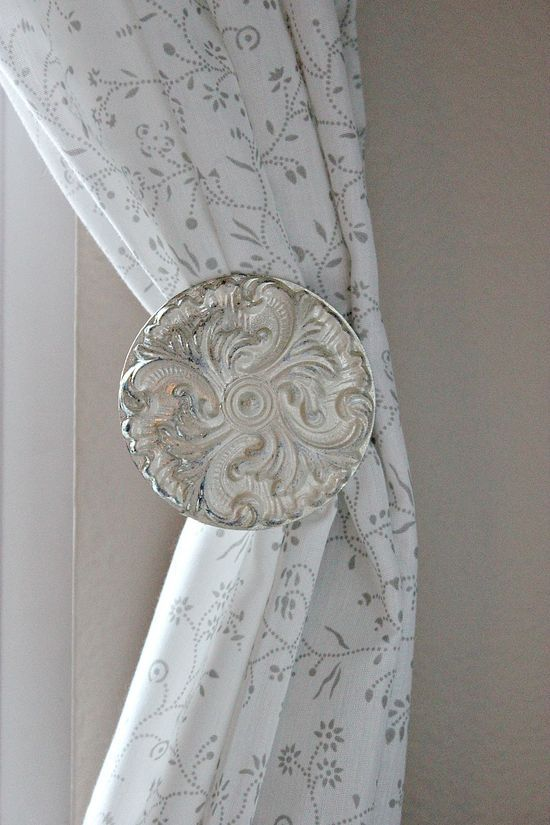 Painted curtain holdbacks in white and silver.