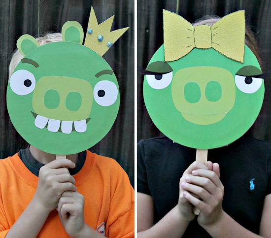 Kids holding Bad Piggies handmade photo props in front of their faces.