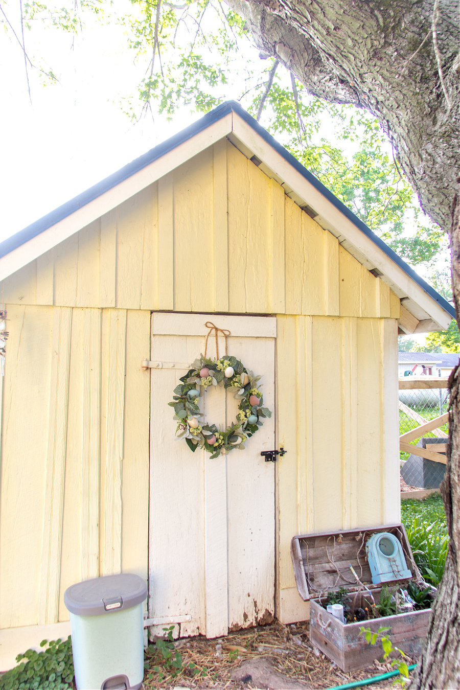A yellow and white garden shed with a blue roof that has been turned into a chicken coop. There is a handmade egg wreath hanging on the door.