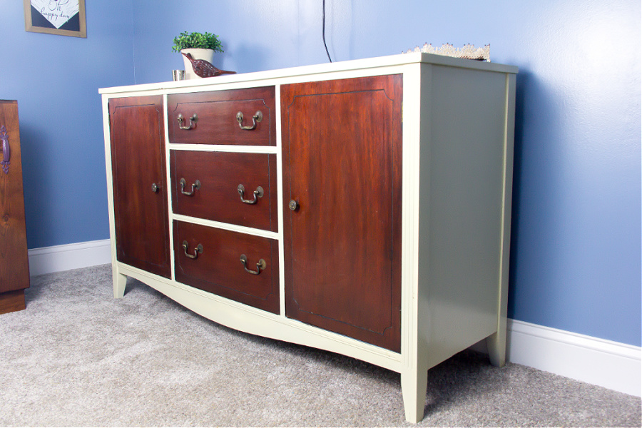 A beautiful dark wood dresser that sections of it have been painted white.