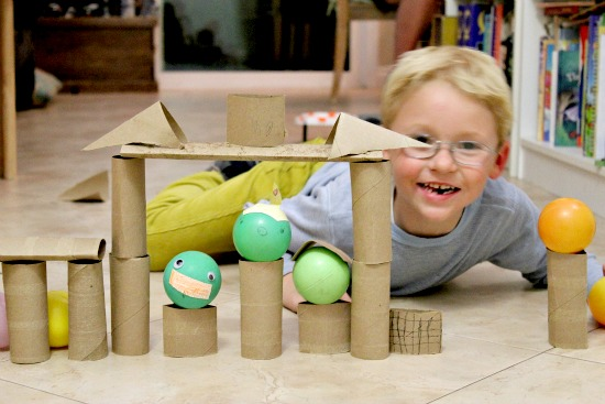 A boy playing with an Angry Birds craft and game using paper rolls.