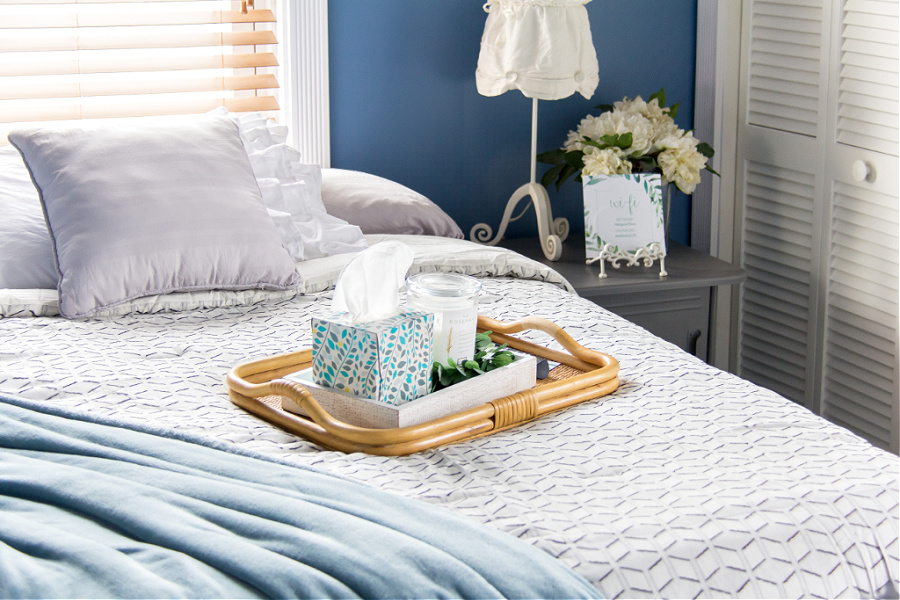 A bed with a tray that has tissues, candles, and remote controls on it in a guest bedroom