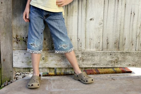 A little boy wearing jeans that have been cut off into shorts and hemmed with cool fabric.