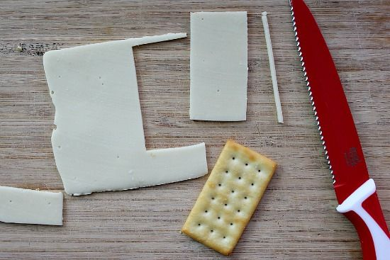 Cheese cut into rectangular slices to place on top of crackers.