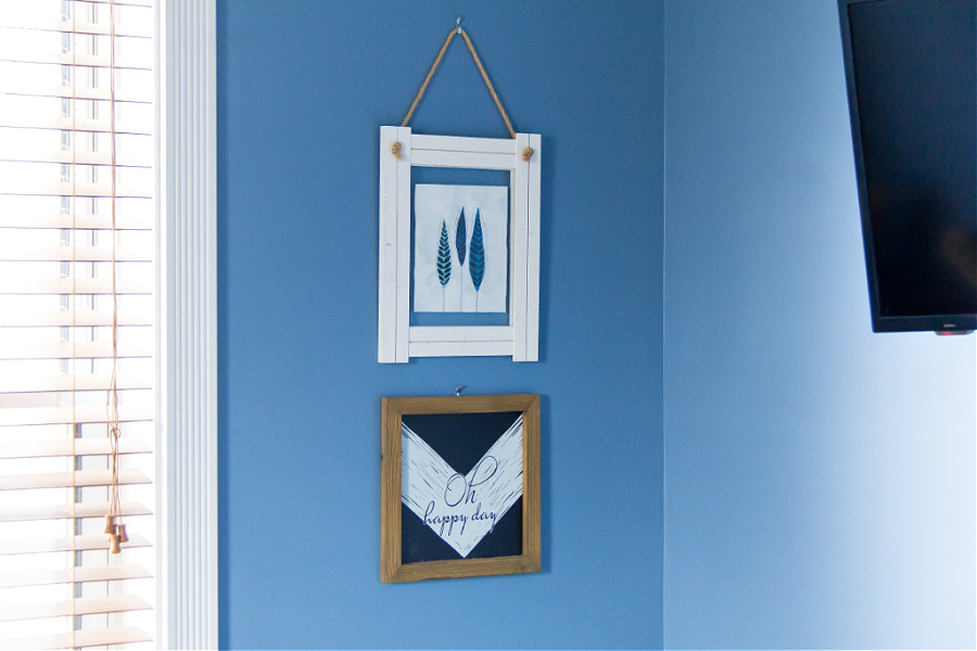 Artwork hanging on a blue wall in a guest bedroom.