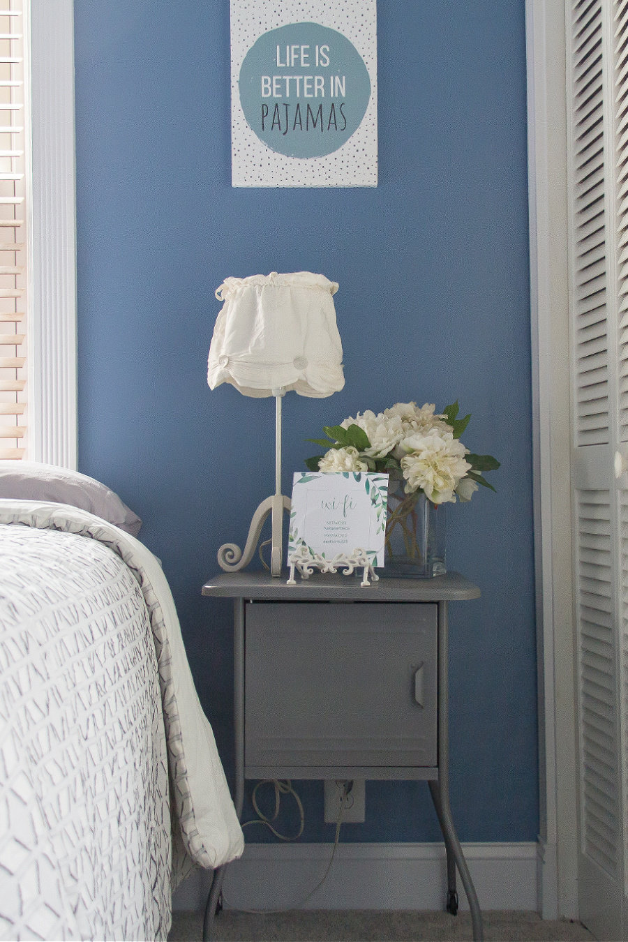 A grey metal bedside table with white flowers in a vase, a white bedside lamp, and a card with passwords for a guest bedroom.