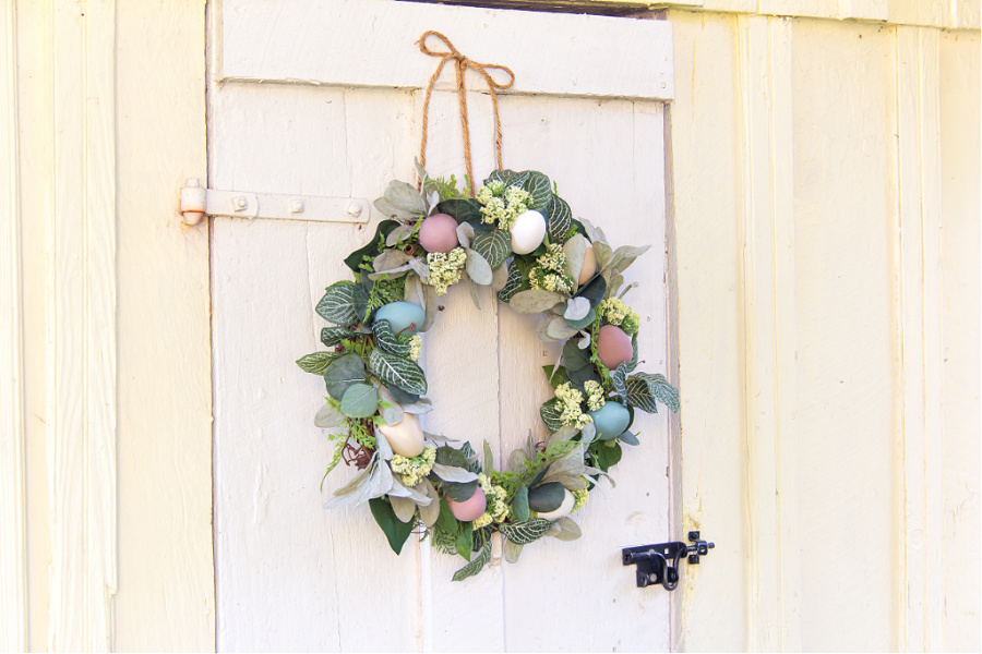 A green leaf and wood egg wreath hanging on a chicken coop door.