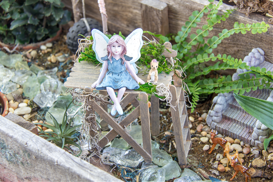 A fairy sitting on top of an observation deck made out of popsicle sticks. It's sitting inside a fairy garden with deer underneath.