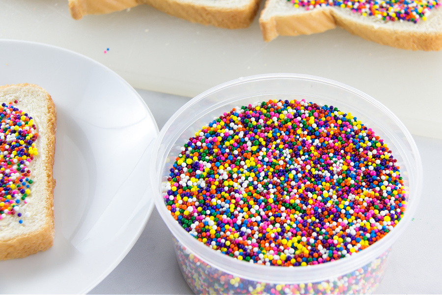A container of hundreds and thousands next to fairy bread being made.