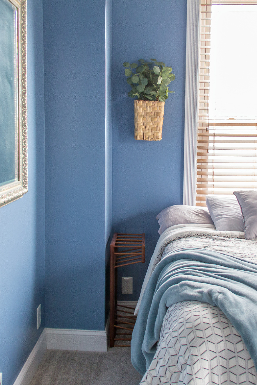 A bed with a TV dinner tray, a basket of greenery on the wall and a throw blanket in a guest bedroom.