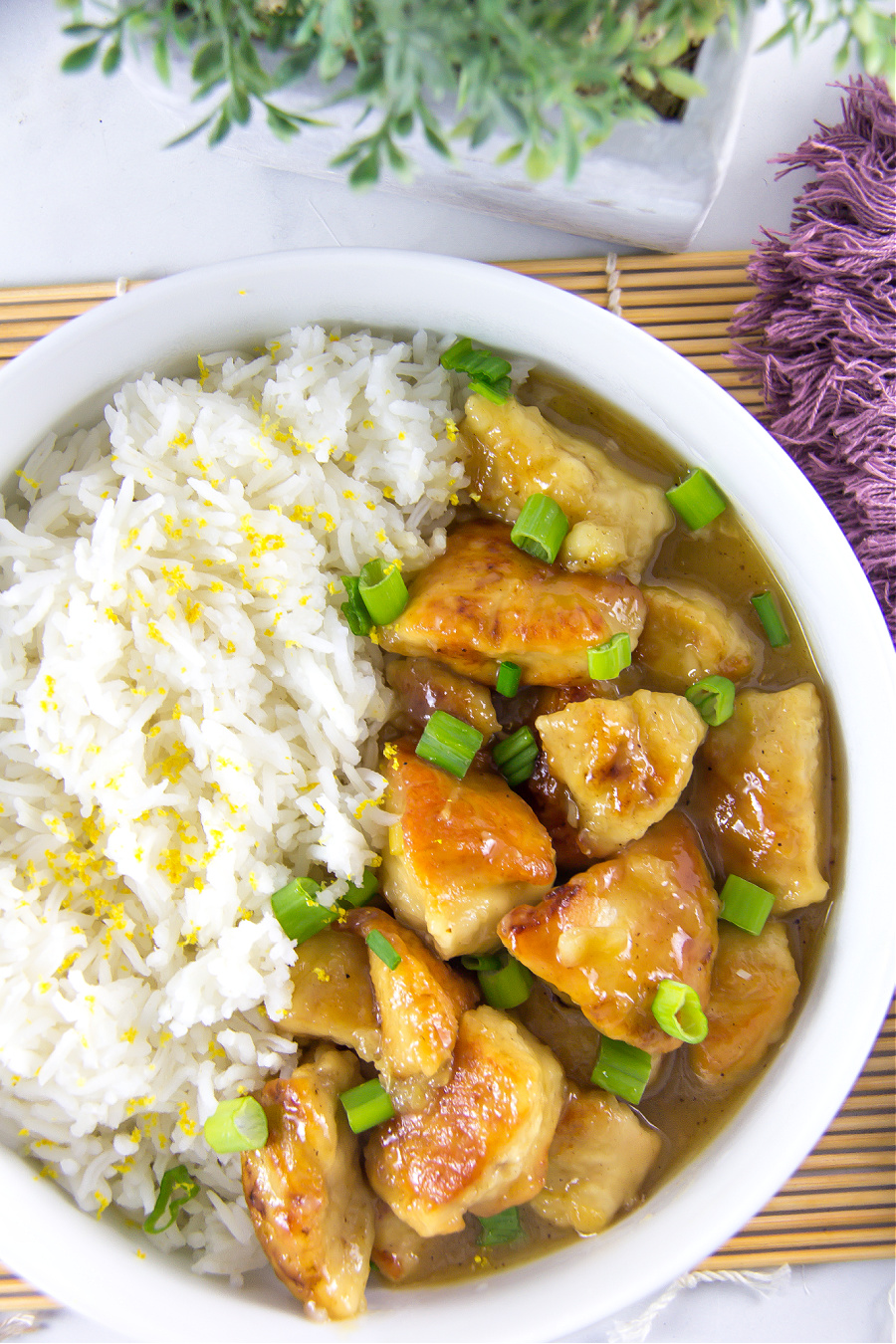 Homemade lemon chicken garnished with green onions in a bowl and served with white rice garnished with lemon rind.