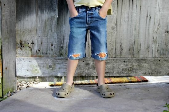 A boy wearing a pair of cut-off denim shorts with knee holes patched with orange fleece.