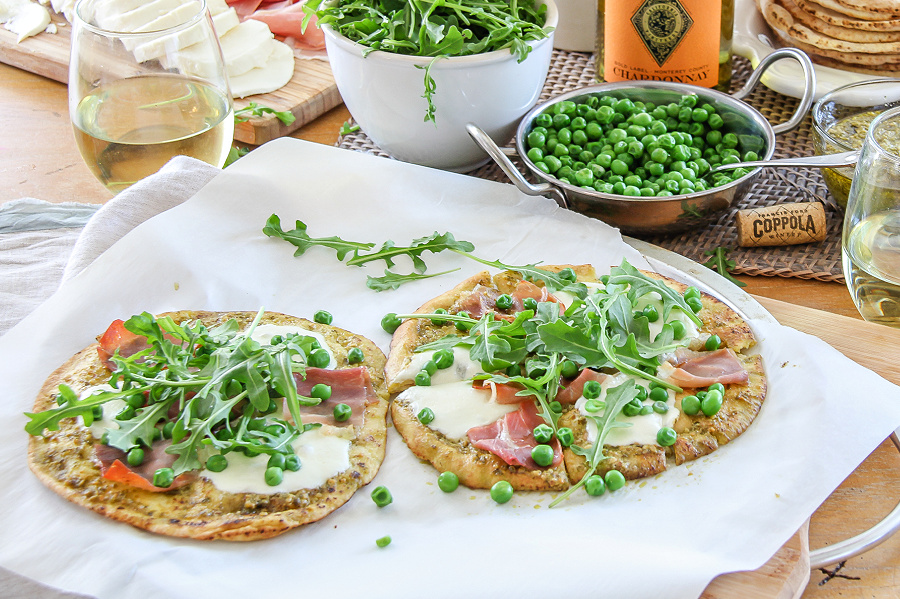 Two naan pizzas topped with peas arugula and prosciutto