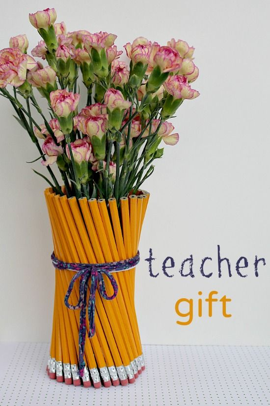 A vase with flowers that has been wrapped with writing pencils for a teacher gift.