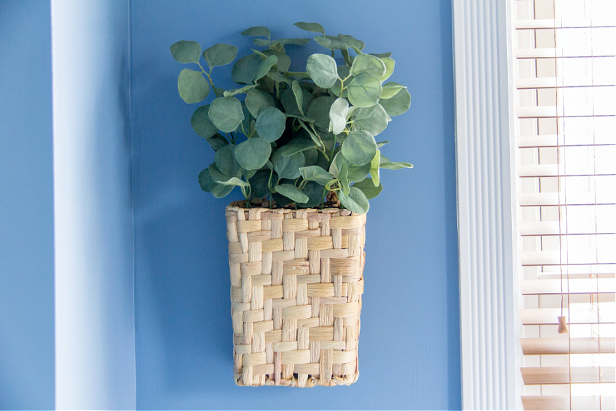 A blue bedroom wall with a basket full of greenery hanging on the wall.