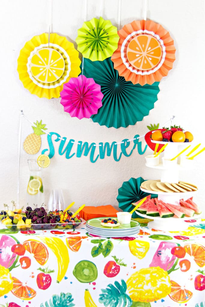 A party table for summer that is fruit themed with a tablecloth, decorations on the wall and fresh fruit ideas.