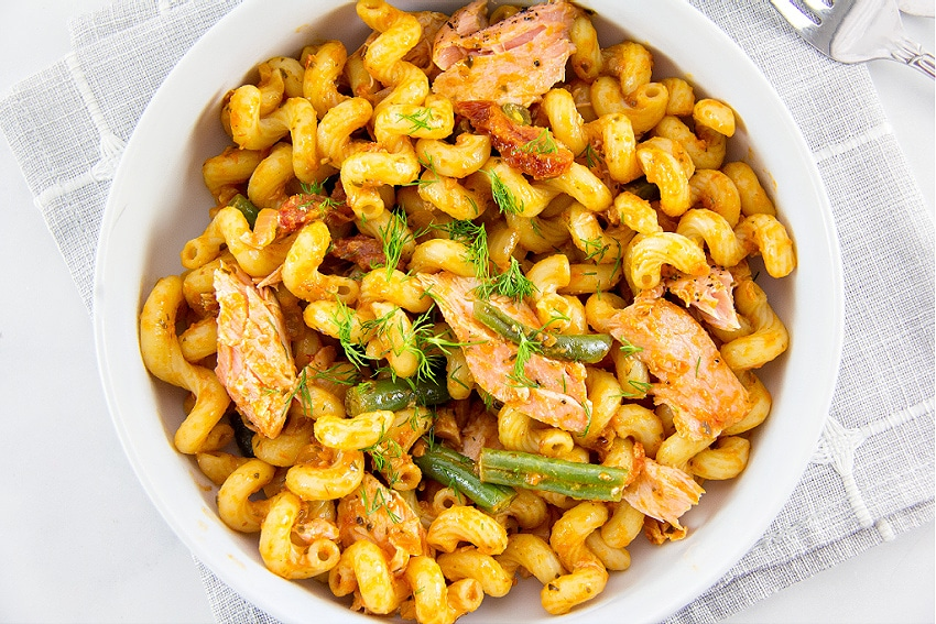 Salmon with sundried tomato pesto with cellentani pasta in a bowl.