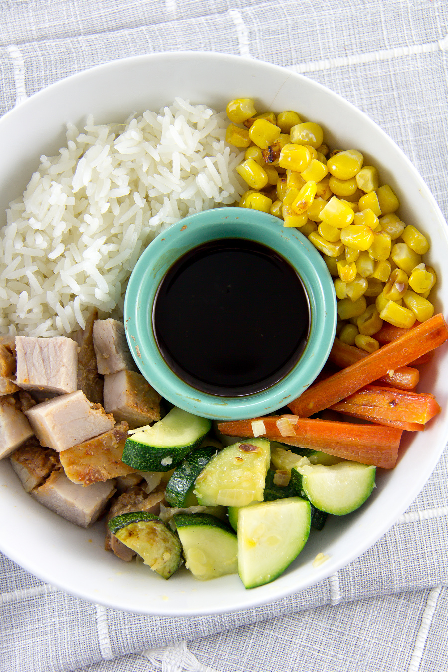 A bowl filled with rice, pork, zucchini, carrots and corn.